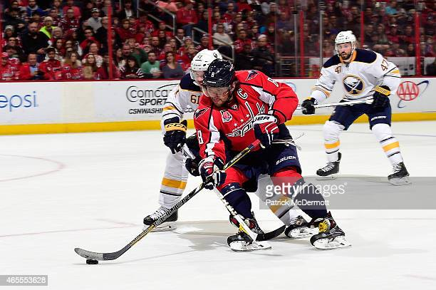 Alex Ovechkin of the Washington Capitals moves the puck up ice against Andre Benoit of the Buffalo Sabres in the second period during an NHL game at...