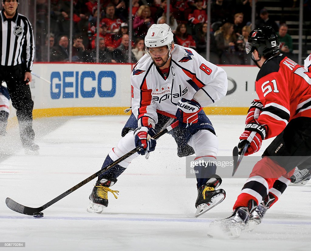 Alex Ovechkin #8 of the Washington Capitals passes the puck as Sergey Kalinin #51 of the New Jersey Devils defends on February 6, 2016 at Prudential Center in Newark, New Jersey.