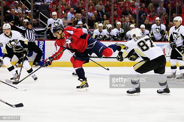 Alex Ovechkin of the Washington Capitals passes the puck in front of Sidney Crosby of the Pittsburgh Penguins at Verizon Center on November 20 2013...