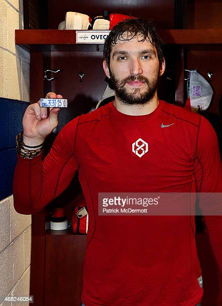 Alex Ovechkin of the Washington Capitals poses with a puck commemorating his 50th goal of the season after an NHL game against the Carolina...