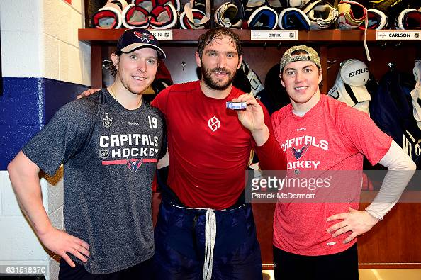 Alex Ovechkin of the Washington Capitals poses with the puck commemorating his 1000th career NHL point from his first period goal with teammates...