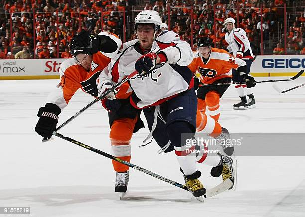 Alex Ovechkin of the Washington Capitals pushes his way past Kimmo Timonen of the Phildelphia Flyers at the Wachovia Center on October 6 2009 in...