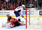 Alex Ovechkin of the Washington Capitals scores the game winner in an overtime shootout as Cory Schneider of the New Jersey Devils is unable to stop...