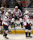 Alex Ovechkin of the Washington Capitals sits on the dasher board during a break in the action along with Evgeny Kuznetsov Nicklas Backstrom and head...