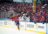 Alex Ovechkin of the Washington Capitals skates by the Capitals bench to celebrate with teammates after a goal scored by teammate Troy Brouwer during...