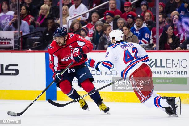 Alex Ovechkin of the Washington Capitals skates with the puck against Brendan Smith of the New York Rangers in the first period at Capital One Arena...