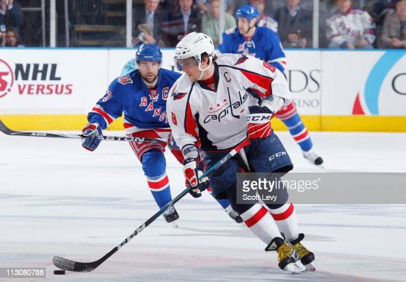 Alex Ovechkin of the Washington Capitals skates with the puck under pressure by Chris Drury of the New York Rangers in Game Four of the Eastern...