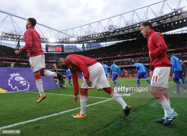 Alex OxladeChamberlain Alexandre Lacazette and Mesut Ozil of Arsenal walk out before the Premier League match between Arsenal and Leicester City at...