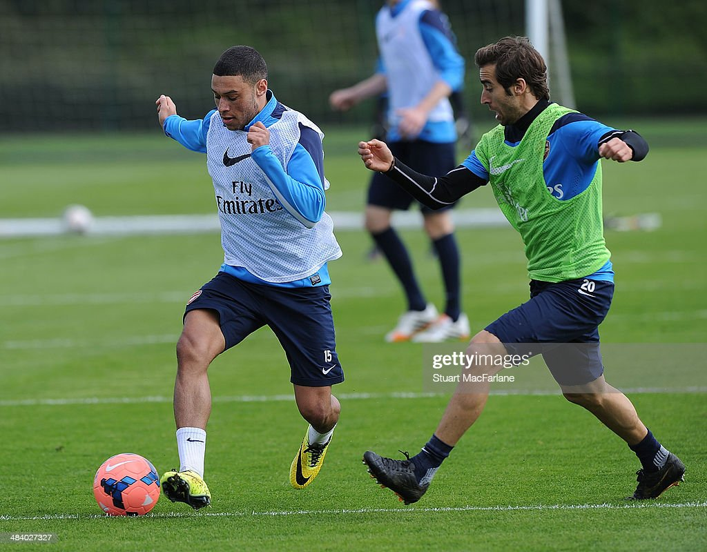 Alex Oxlade-Chamberlain and Mathieu Flamini of Arsenal during a training session at London Colney on April 11, 2014 in St Albans, England.