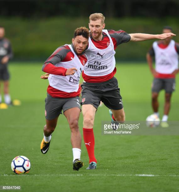 Alex OxladeChamberlain and Per Mertesacker of Arsenal during a training session at London Colney on August 2 2017 in St Albans England