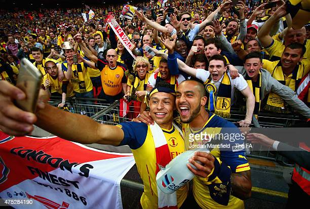 Alex OxladeChamberlain and Theo Walcott of Arsenal take a selfie with their fans after winning the FA Cup Final between Aston Villa and Arsenal at...