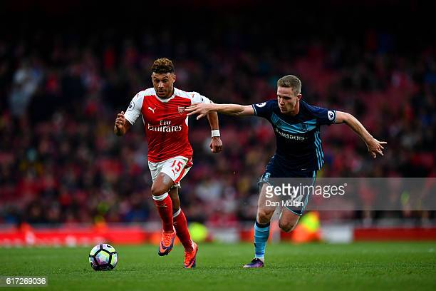 Alex OxladeChamberlain of Arsenal and Adam Forshaw of Middlesbrough battle for possession during the Premier League match between Arsenal and...
