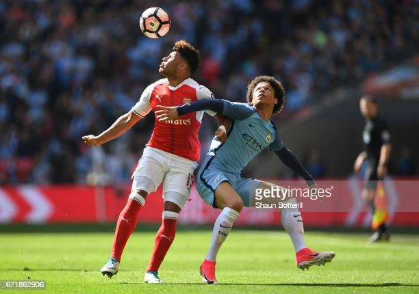 Alex OxladeChamberlain of Arsenal and Leroy Sane of Manchester City compete for the ball during the Emirates FA Cup SemiFinal match between Arsenal...