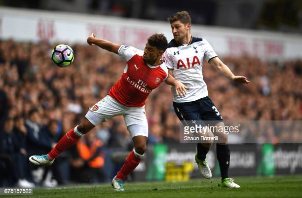 Alex OxladeChamberlain of Arsenal attempts to control the ball while under pressure from Ben Davies of Tottenham Hotspur during the Premier League...