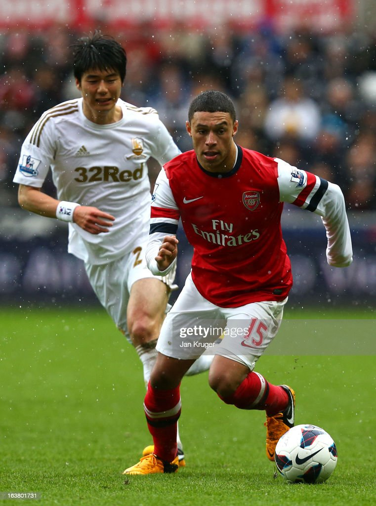 <a gi-track='captionPersonalityLinkClicked' href=/galleries/search?phrase=Alex+Oxlade-Chamberlain&family=editorial&specificpeople=7191518 ng-click='$event.stopPropagation()'>Alex Oxlade-Chamberlain</a> of Arsenal battles with Ki Sung-Yueng of Swansea City during the Barclays Premier League match between Swansea City and Arsenal at Liberty Stadium on March 16, 2013 in Swansea, Wales.