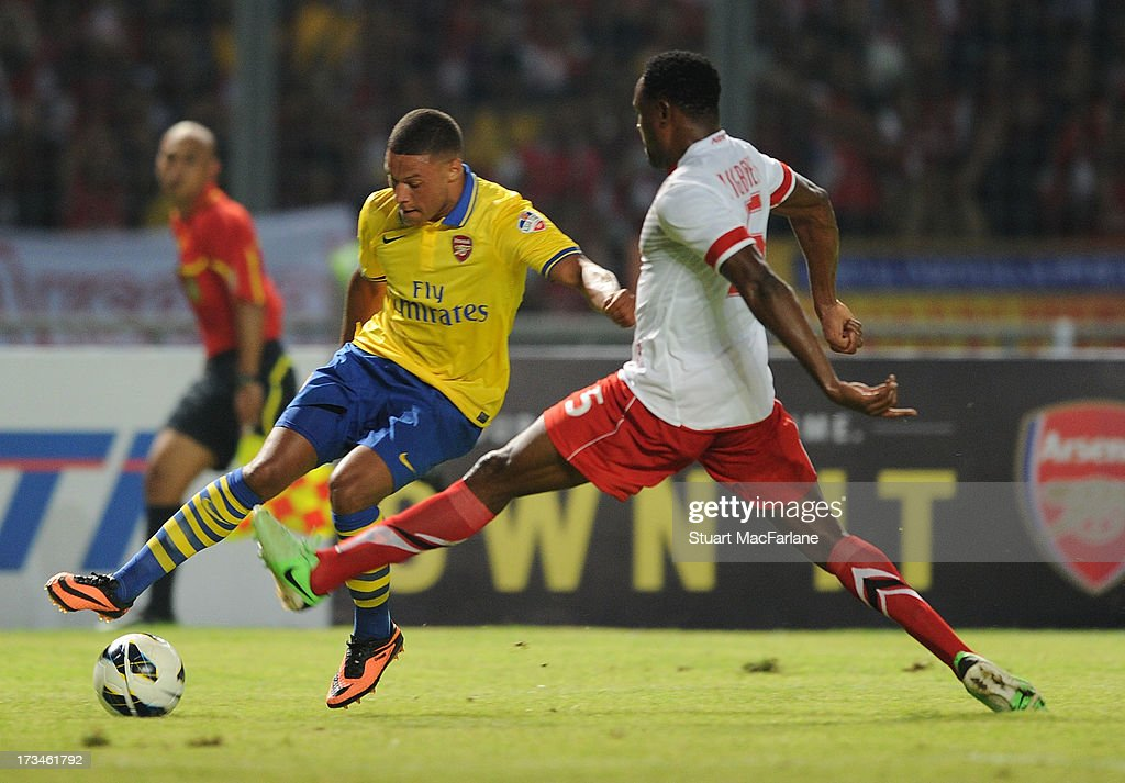 Alex Oxlade-Chamberlain of Arsenal breaks past Victor Igbonefo of Indonesia during the match between Arsenal and the Indonesia All-Stars at Gelora Bung Karno Stadium on July 14, 2013 in Jakarta, Indonesia.