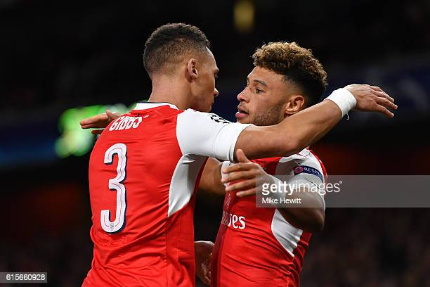 Alex OxladeChamberlain of Arsenal celebrates with team mate Kieran Gibbs after scoring his team's third goal of the game during the UEFA Champions...