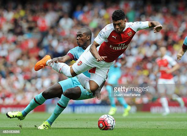Alex OxladeChamberlain of Arsenal challenged by Angelo Ogbonna of West Ham during the Barclays Premier League match between Arsenal and West Ham...