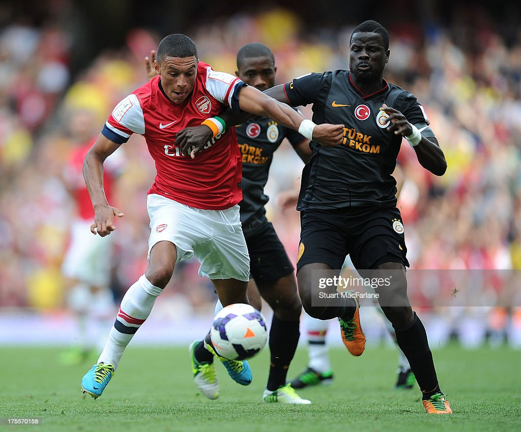 Alex Oxlade-Chamberlain of Arsenal challenged by Emmanuel Eboue of Galatasaray during the Emirates Cup match between Arsenal and Galatasaray at the Emirates Stadium on August 04, 2013 in London, England.