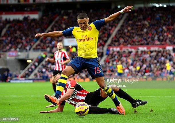 Alex OxladeChamberlain of Arsenal holds off the challenge from Lee Cattermole of Sunderland during the Barclays Premier League match between...