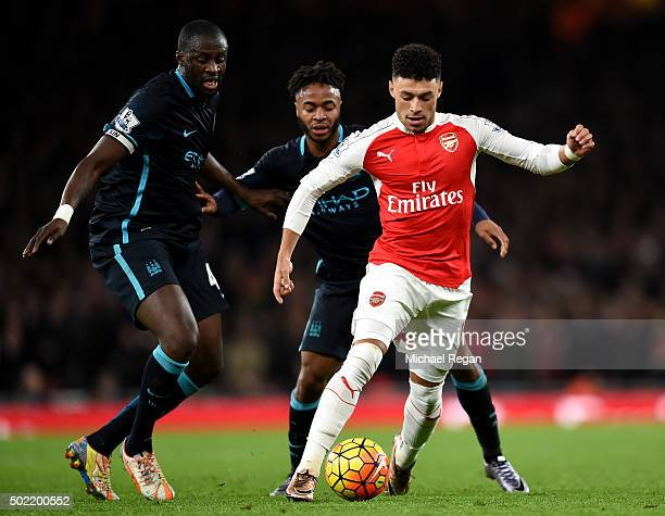 Alex OxladeChamberlain of Arsenal holds off Yaya Toure and Raheem Sterling of Manchester City during the Barclays Premier League match between...