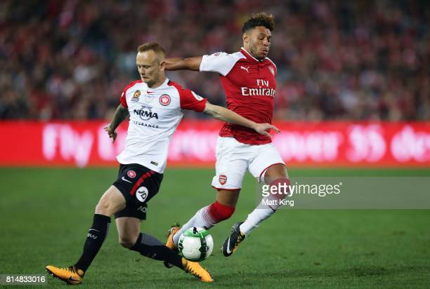 Alex OxladeChamberlain of Arsenal is challenged by Jack Clisby of the Wanderers during the match between the Western Sydney Wanderers and Arsenal FC...