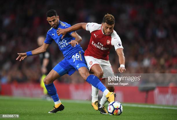 Alex OxladeChamberlain of Arsenal is challenged by Riyad Mahrez of Leicester City during the Premier League match between Arsenal and Leicester City...