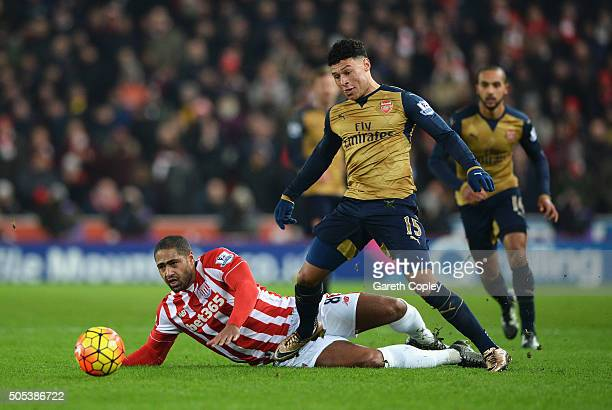 Alex OxladeChamberlain of Arsenal is tackled by Glen Johnson of Stoke City during the Barclays Premier League match between Stoke City and Arsenal at...