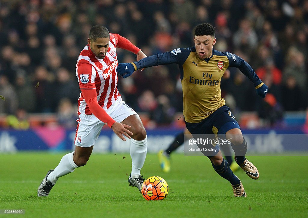 Alex Oxlade-Chamberlain of Arsenal is tackled by Glen Johnson of Stoke City during the Barclays Premier League match between Stoke City and Arsenal at Britannia Stadium on January 17, 2016 in Stoke on Trent, England.