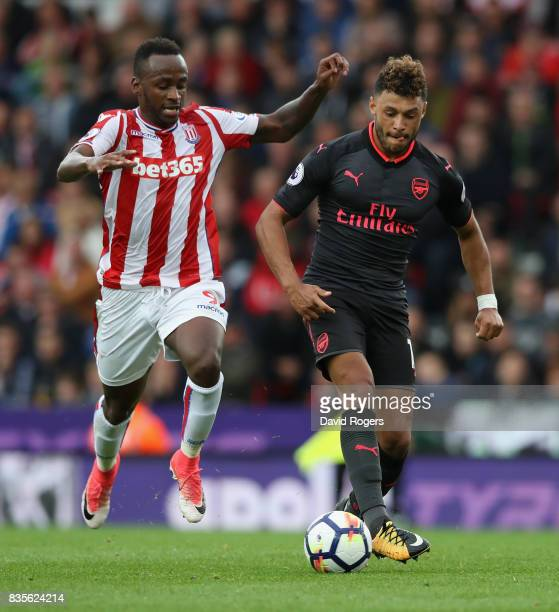 Alex OxladeChamberlain of Arsenal moves away from Saido Berahino during the Premier League match between Stoke City and Arsenal at Bet365 Stadium on...