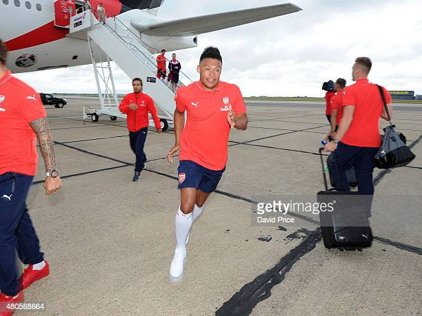Alex OxladeChamberlain of Arsenal runs to collect his bag before boarding the plane at Stansted Airport on July 12 2015 in London England