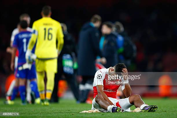 Alex OxladeChamberlain of Arsenal sits dejected after the UEFA Champions League Group F match between Arsenal FC and Olympiacos FC at the Emirates...