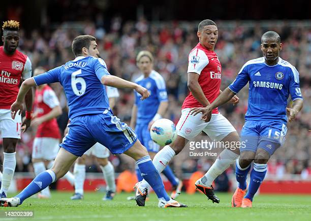 Alex OXladeChamberlain of Arsenal slips the ball between Oriol Romeu and Florent Malouda of Chelsea during the Barclays Premier League match between...