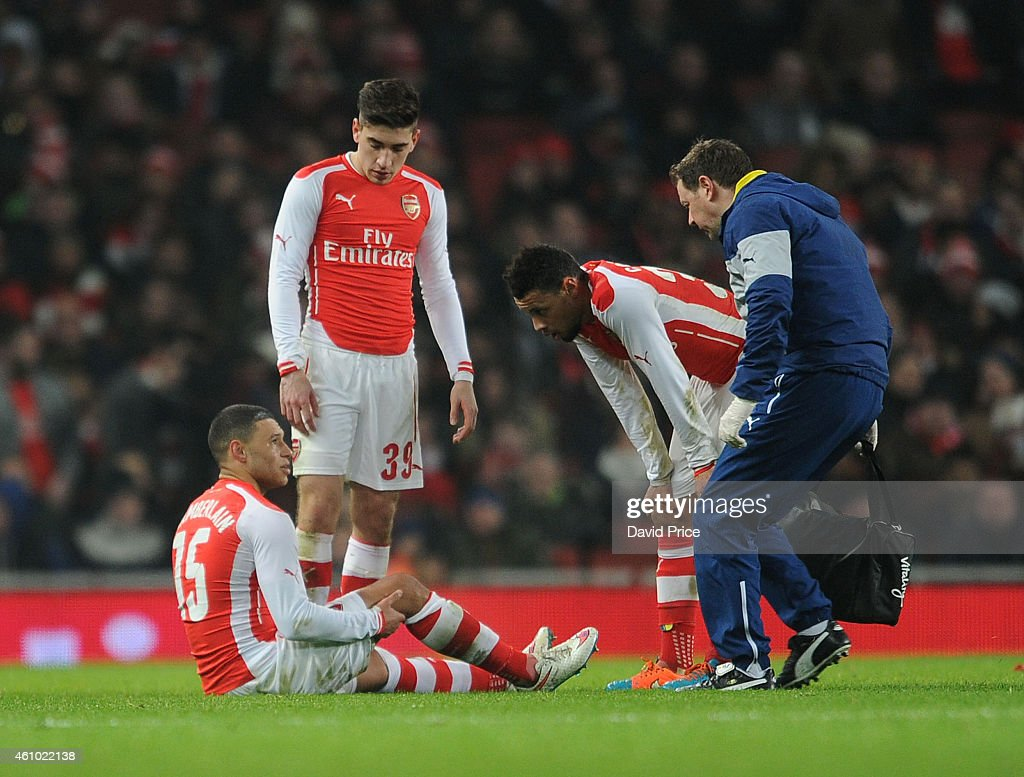 Alex Oxlade-Chamberlain of Arsenal speaks to Arsenal Physio Colin Lewin as Hector Bellerin and Francis Coquelin look on during the match between Arsenal and Hull City in the FA Cup 3rd Round at Emirates Stadium on January 4, 2015 in London, England.