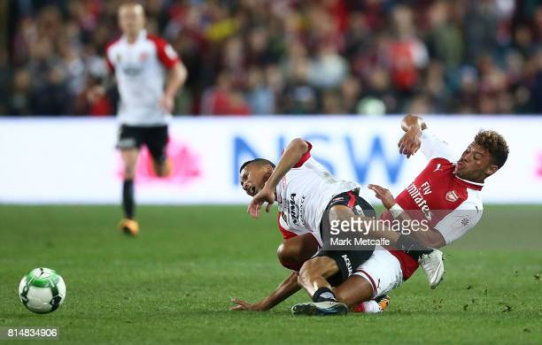 Alex OxladeChamberlain of Arsenal tackles Kearyn Baccus of the Wanderers during the match between the Western Sydney Wanderers and Arsenal FC at ANZ...