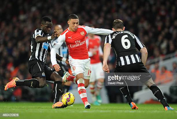 Alex OxladeChamberlain of Arsenal takes on Cheick Tiote and Mike Williamson of Newcastle during the match between Arsenal and Newcastle United in the...
