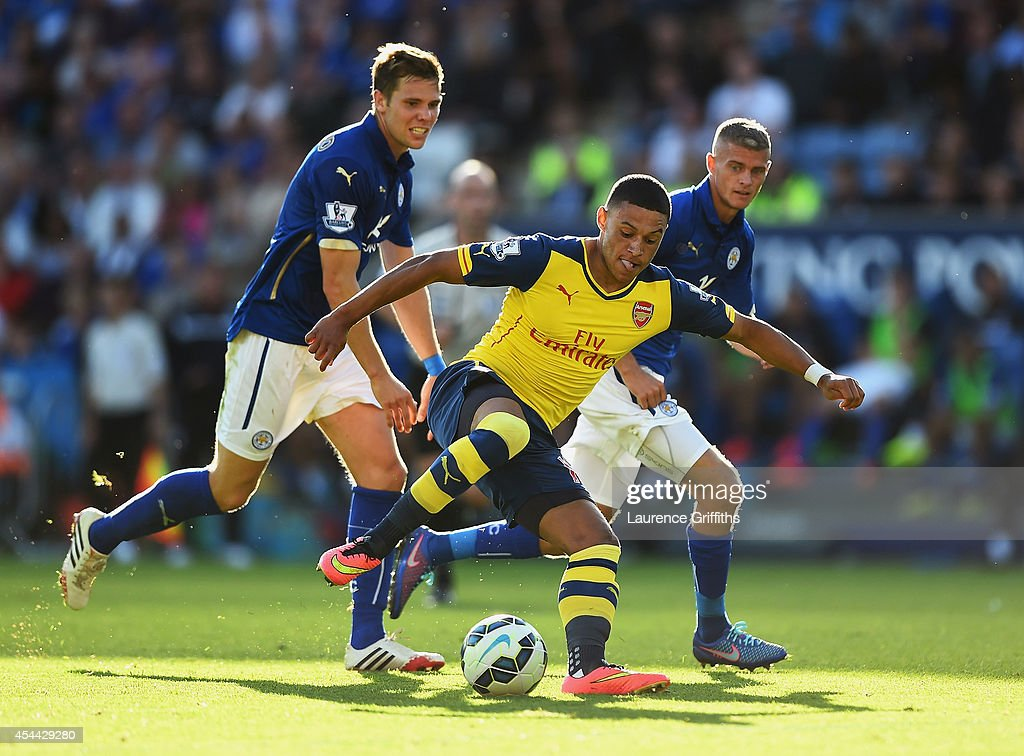 Alex Oxlade-Chamberlain of Arsenal takes on Dean Hammond and Paul Konchesky of Leicester City during the Barclays Premier League match between Leicester City and Arsenal at The King Power Stadium on August 31, 2014 in Leicester, England.