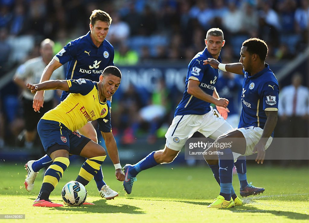 Alex Oxlade-Chamberlain of Arsenal takes on Dean Hammond, Paul Konchesky and Liam Moore of Leicester City during the Barclays Premier League match between Leicester City and Arsenal at The King Power Stadium on August 31, 2014 in Leicester, England.