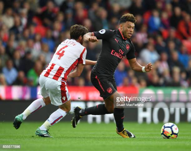 Alex OxladeChamberlain of Arsenal takes on Joe Allen of Stoke during the Premier League match between Stoke City and Arsenal at Bet365 Stadium on...