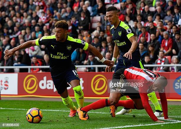 Alex OxladeChamberlain of Arsenal takes the ball away from Wahbi Khazri of Sunderland and Kieran Gibbs of Arsenal during the Premier League match...