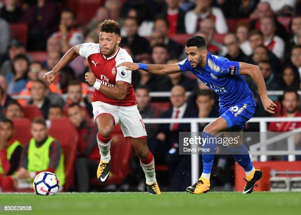 Alex OxladeChamberlain of Arsenal under pressure from Riyad Mahrez of Leicester during the Premier League match between Arsenal and Leicester City at...