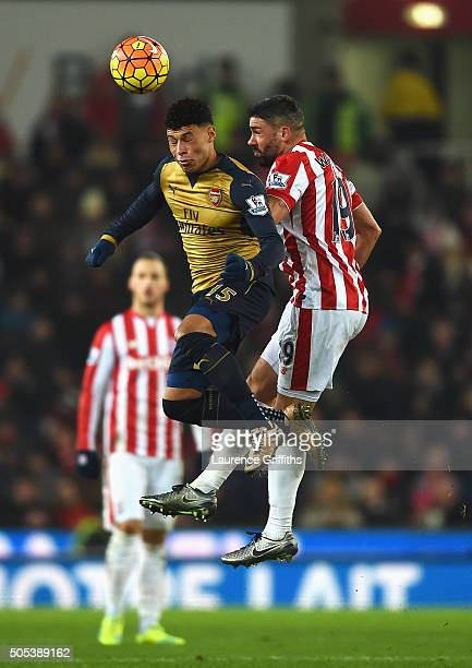 Alex OxladeChamberlain of Arsenal wins a header from Jonathan Walters of Stoke City during the Barclays Premier League match between Stoke City and...