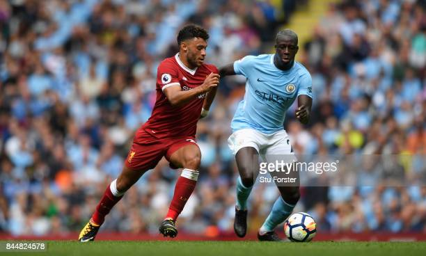 Alex OxladeChamberlain of Liverpool and Benjamin Mendy of Manchester City battle for possession during the Premier League match between Manchester...