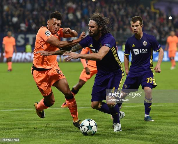 Alex OxladeChamberlain of Liverpool competes with Marko Suler of NK Mariborduring the UEFA Champions League group E match between NK Maribor and...