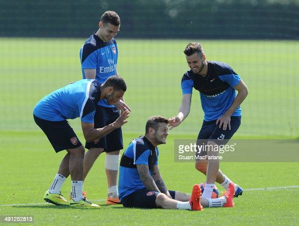 Alex OxladeChamberlain Thomas Vermaelen Jack Wilshere and Carl Jenkinson of Arsenal joke around during a training session at London Colney on May 16...