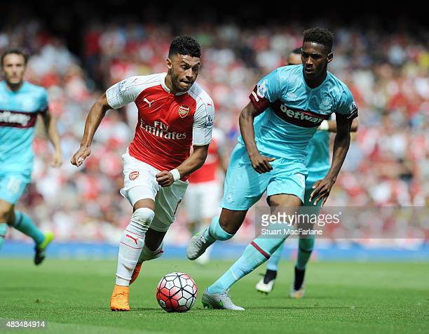 Alex OxladeChambrlain of Arsenal breaks past Reece Oxford of West Ham during the Barclays Premier League match between Arsenal and West Ham United at...