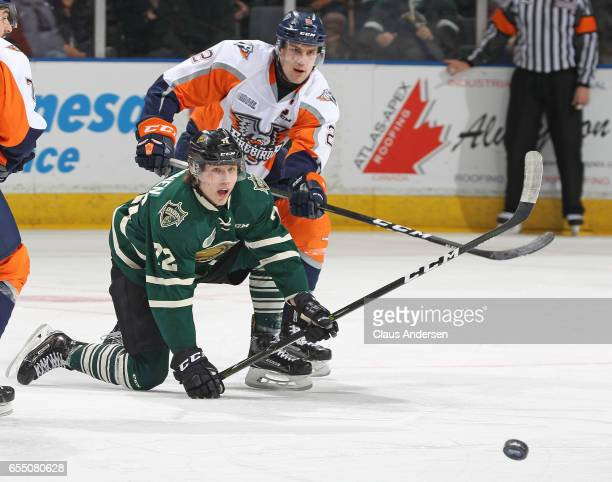 Alex Peters of the Flint Firebirds battles for a loose puck against Janne Kuokkanen of the London Knights during an OHL game at Budweiser Gardens on...