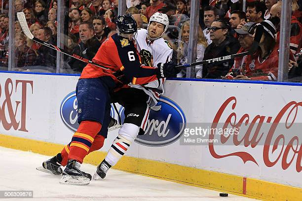 Alex Petrovic of the Florida Panthers checks Andrew Desjardins of the Chicago Blackhawks during a game at BBT Center on January 22 2016 in Sunrise...