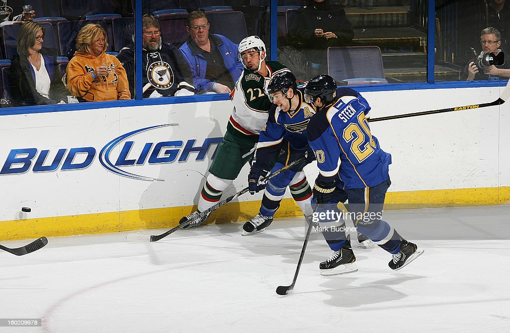 Alex Pietrangelo #27 and Alexander Steen #20 of the St. Louis Blues battle Cal Clutterbuck #22 of the Minnesota Wild for the lose puck in an NHL game on January 27, 2013 at Scottrade Center in St. Louis, Missouri.