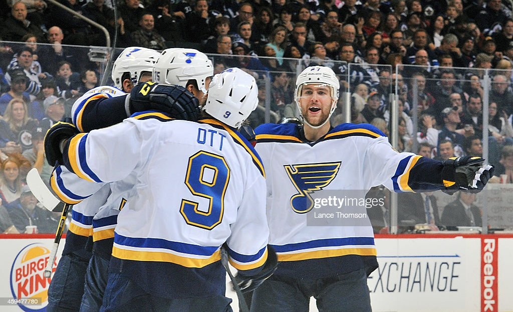 Alex Pietrangelo of the St Louis Blues joins teammates Maxim Lapierre Ryan Reaves and Steve Ott to celebrate a third period goal against the Winnipeg...